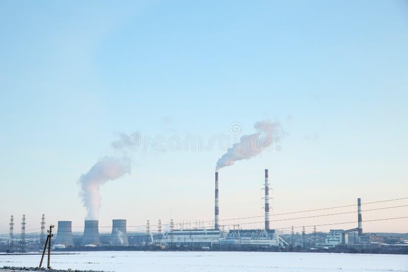 centrale elettrica termica di fumo dei fumaioli sui precedenti del cielo blu fotografia stock