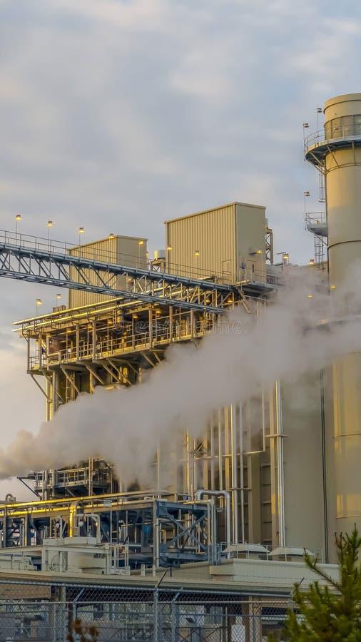 Centrale elettrica verticale che libera vapore contro il cielo blu-chiaro con le nuvole gonfie luminose fotografia stock libera da diritti