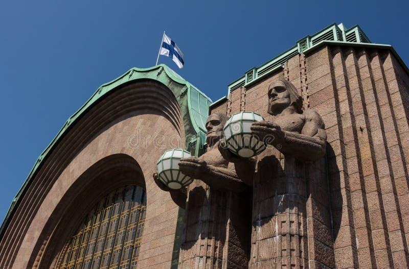 Centrale het stationstandbeelden en vlag van Helsinki stock foto