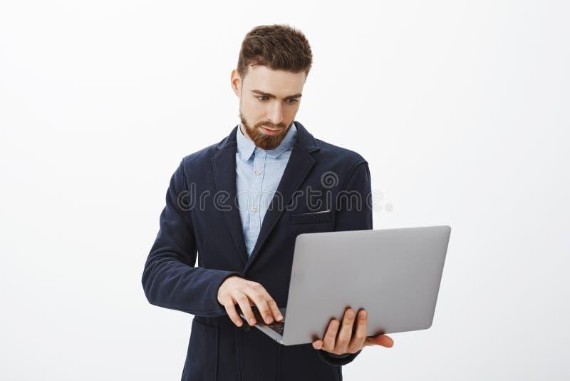 Centrar-se sobre o negócio Retrato do empresário masculino novo bonito concentrado esperto e ambicioso com barba e foto de stock