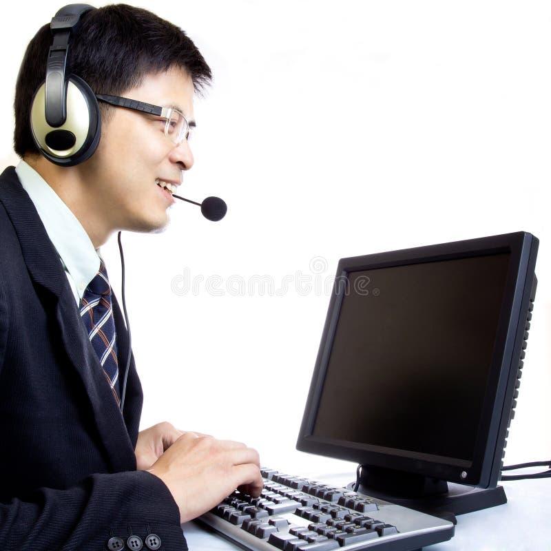 Centre d'attention téléphonique asiatique d'homme avec le casque de téléphone photographie stock