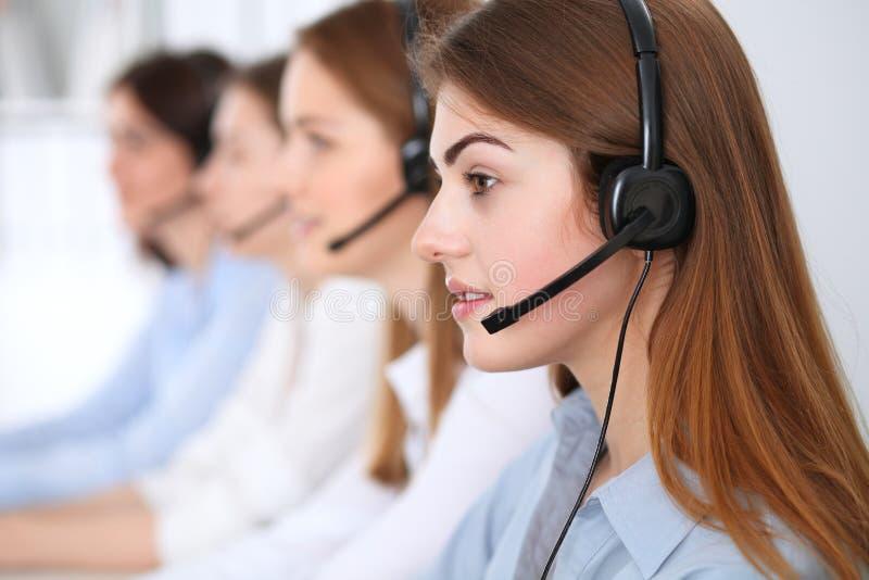 Centre d'attention téléphonique Beaux clients de consultation de sourire gais d'opérateur avec le casque Concept d'affaires de se photos stock