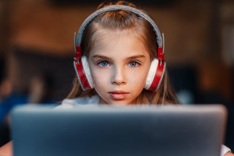 Centre de petite fille dans des écouteurs utilisant l'ordinateur portable photographie stock