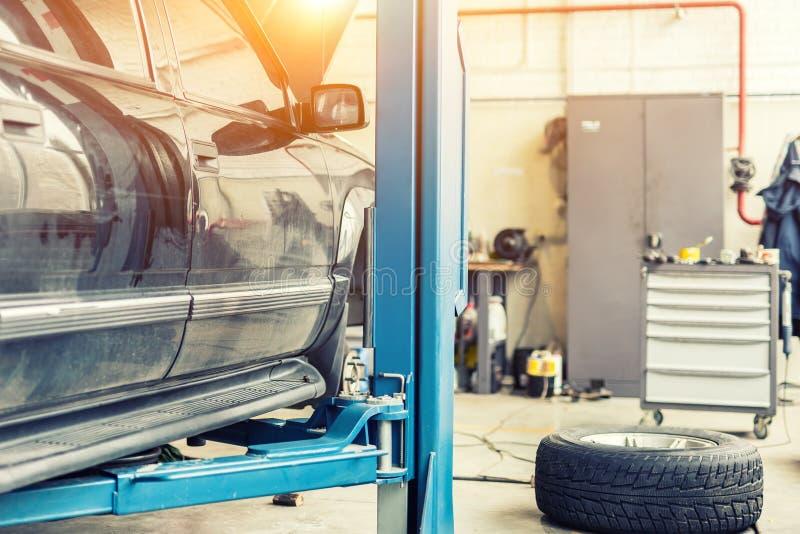 Centre de service de voiture Le vieux véhicule tous terrains rouillé de SUV a augmenté sur l'ascenseur à la station d'entretien R photo stock