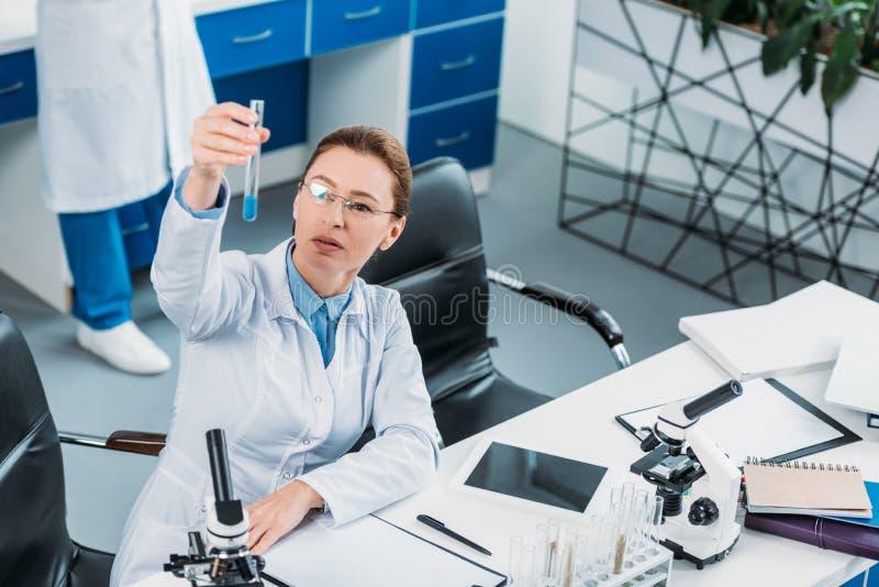 centre sélectif de chercheur féminin regardant le tube avec du réactif à disposition avec le collègue derrière images stock