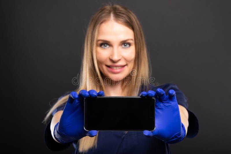 Centre sélectif de docteur féminin montrant le smartphone images libres de droits
