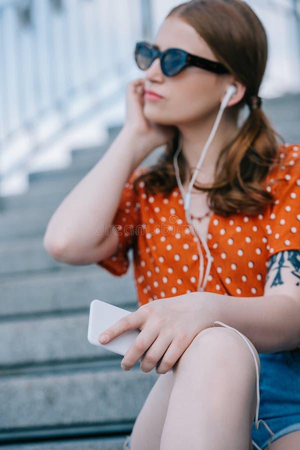 centre sélectif de fille dans la musique de écoute de lunettes de soleil et d'écouteurs avec le smartphone tout en se reposant photos stock
