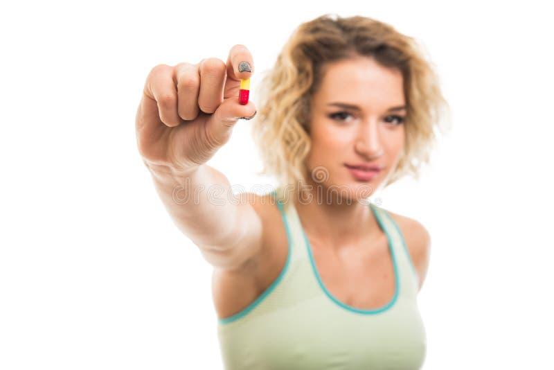 Centre sélectif de la belle jeune fille convenable montrant une pilule photographie stock libre de droits