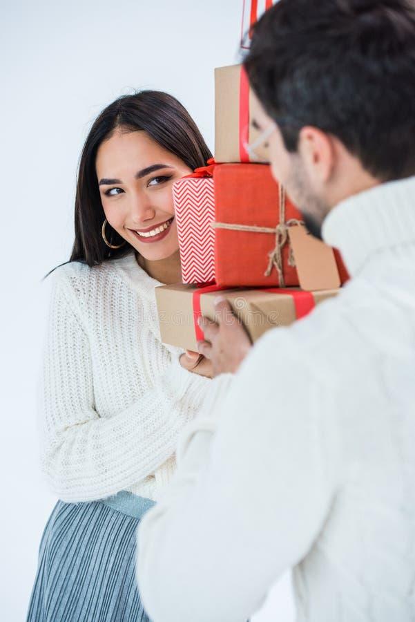 centre sélectif de la pile asiatique de sourire de participation de femme de cadeaux enveloppés de Noël ainsi que l'ami photos stock