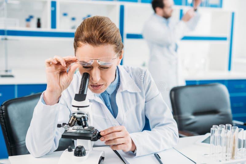 centre sélectif de scientifique féminin regardant par le microscope sur le réactif le lieu de travail avec le collègue derrière photographie stock libre de droits