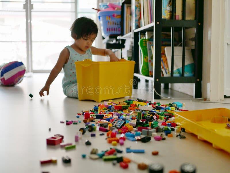 Centre sélectif des blocs de verrouillage étant versés et de la diffusion sur le plancher par le petit bébé asiatique s'asseyant  photographie stock