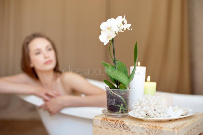 Centre sélectif des bougies et des fleurs sur la table en bois dans le salon de station thermale avec la femme brouillée sur le f photos libres de droits