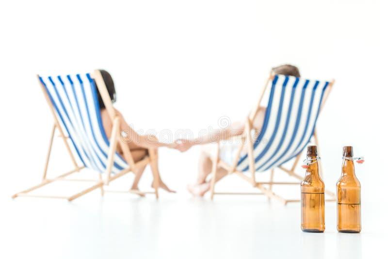 centre sélectif des couples tenant des mains et se reposant sur des chaises de plage, avec des bouteilles de bière sur le premier photos libres de droits