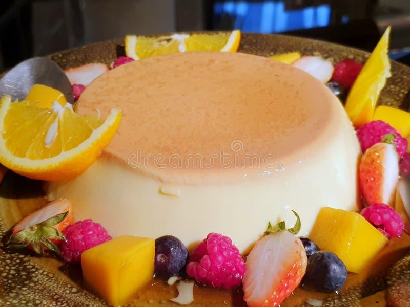 Centre s?lectif de pudding avec les framboises, l'orange, le kiwi, la mangue, la fraise et la pomme comme fond image libre de droits