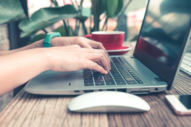 Centre-se sobre a mão da mulher usando o portátil, procurando, verificando, consultando a informação na cafetaria, resíduo metáli foto de stock