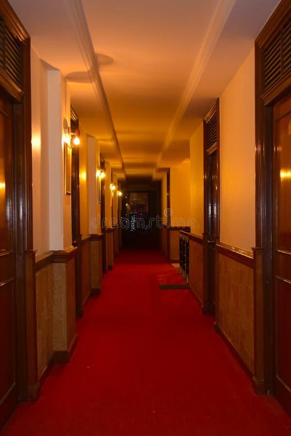 Centrera passagen av ett lyxigt hotell med ljusa väggar och upplysta ljus royaltyfria foton
