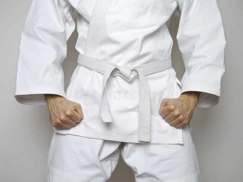 Centrerade det vita bältet för den stående kämpen den vita dräkten för kampsporter royaltyfri foto