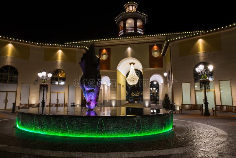 Centro comercial por noche con la fuente de la luz verde con la cabeza de caballo, Italia fotografía de archivo