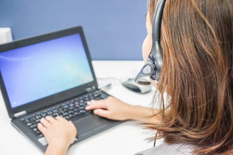 Centro de atención telefónica de la mujer con las auriculares en clientes del servicio del trabajo imagen de archivo libre de regalías