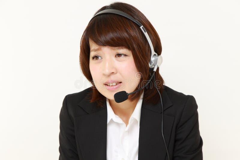 Centro de atención telefónica japonés joven del businesswomanof perplejo a un teléfono de la denuncia imagen de archivo