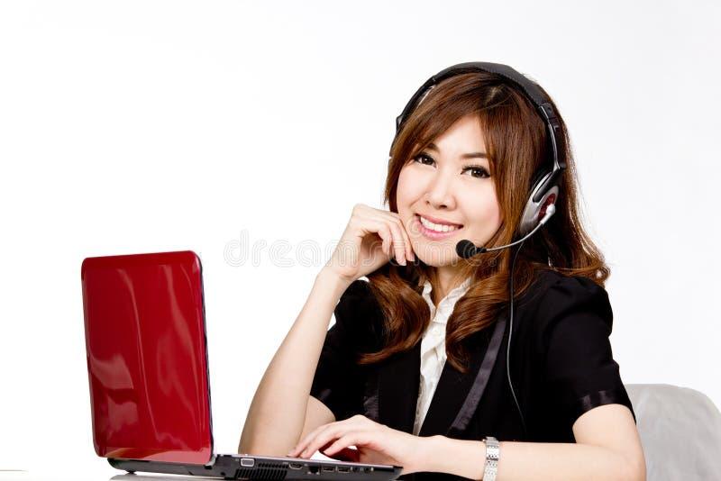 Centro de atendimento asiático das mulheres com auriculares do telefone foto de stock