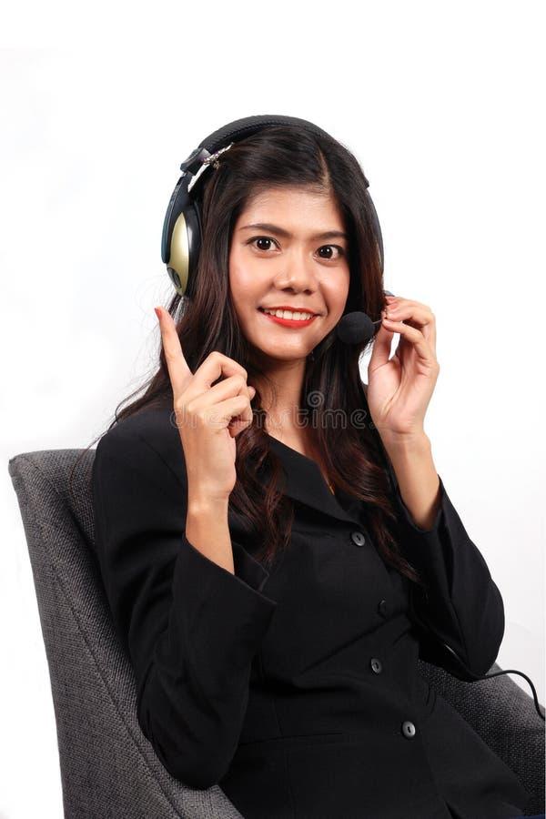 Centro de atendimento asiático das mulheres com os auriculares do telefone com conceito branco do fundo fotografia de stock royalty free