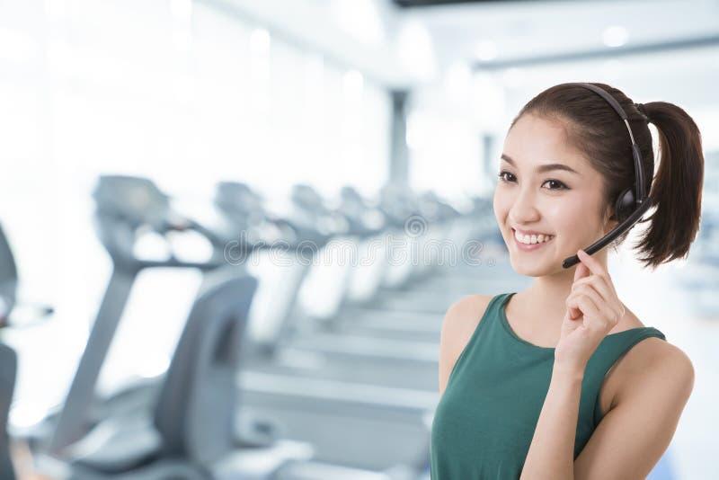 Centro de atendimento asiático do instrutor das mulheres com auriculares do telefone fotografia de stock royalty free