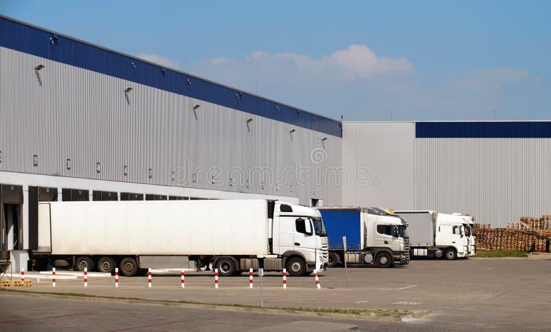 Centro de distribuição Carregamento e descarregamento dos bens em caminhões foto de stock