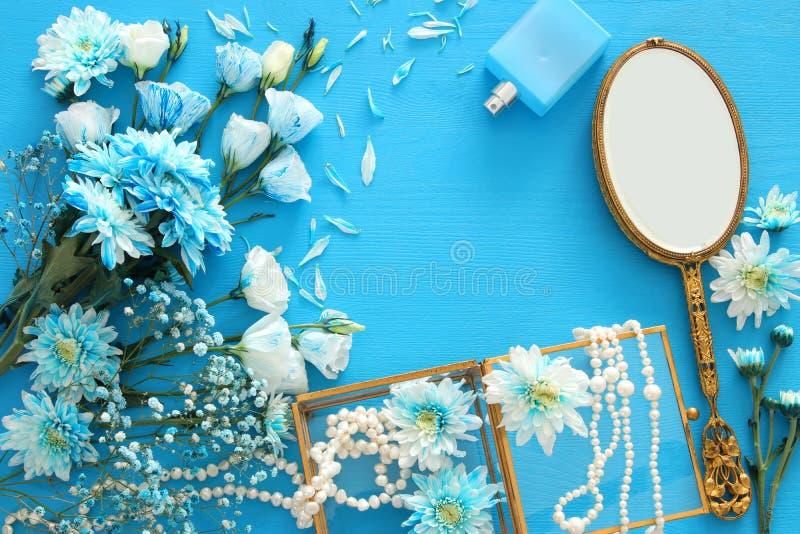 centro de flores azul hermoso y delicado al lado de las perlas collar y del espejo de mano fotografía de archivo