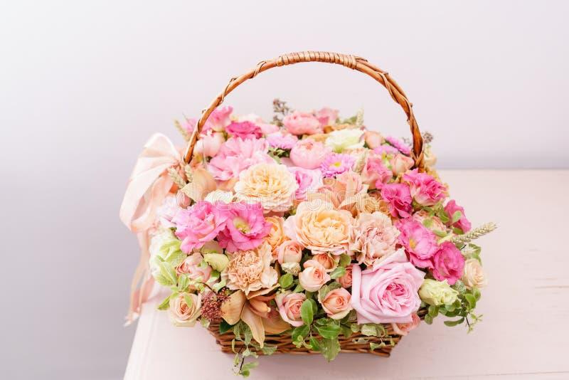Centro de flores con diverso de colores en cesta de mimbre en la tabla rosada Ramo hermoso del resorte sitio brillante, blanco fotografía de archivo libre de regalías