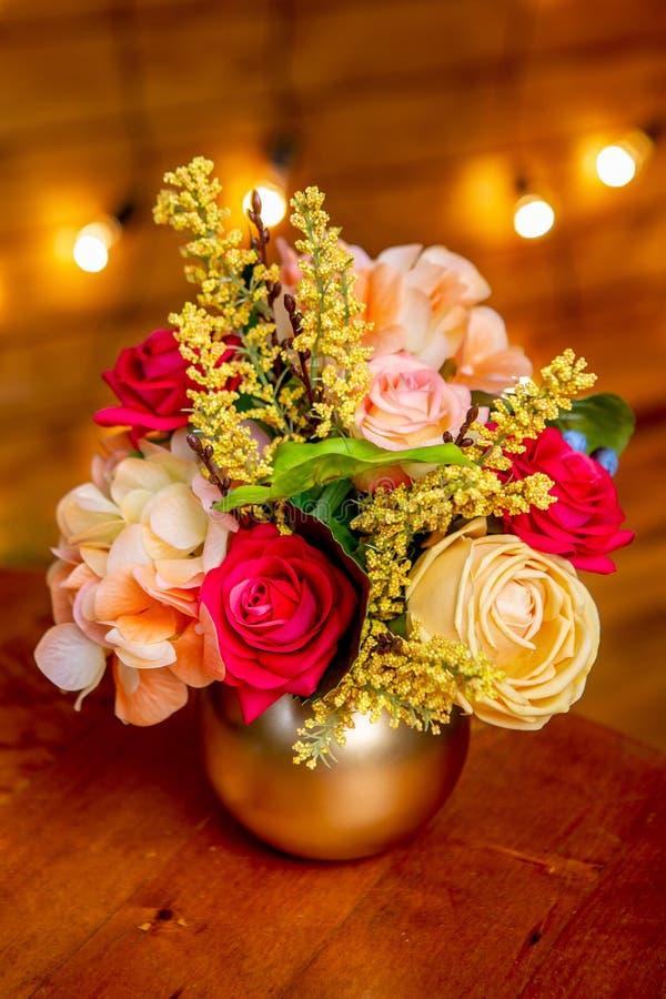 Centro de flores con las rosas, la hortensia, la forsythia y el verdor en un florero en la tabla imagenes de archivo