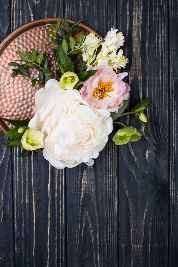Centro de flores de la peonía en viejo fondo del tablero de madera Festiv fotos de archivo libres de regalías