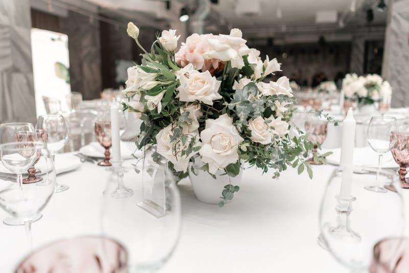 Centro de flores en el centro de la tabla El interior del restaurante para la cena de boda, alista para las hu?spedes redondo imagen de archivo
