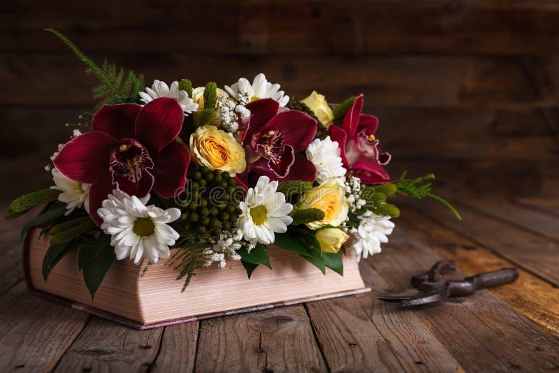 Centro de flores rústico en la tabla de madera fotografía de archivo libre de regalías