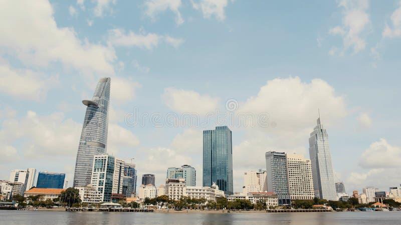 Centro de negócios dos arranha-céus em Ho Chi Minh City em Vietname sobre na perspectiva dos ramos de inclinação das árvores imagem de stock