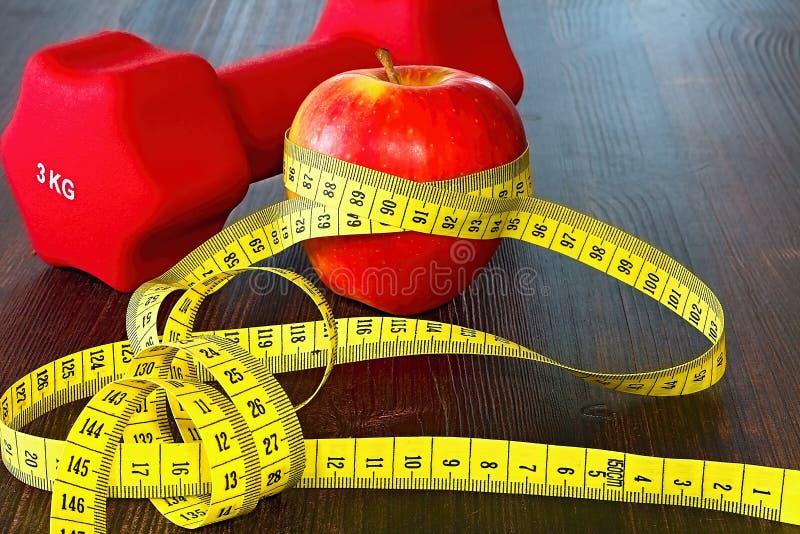 Centro di forma fisica con una mela per lo spuntino dopo l'esercizio, una testa di legno e una metropolitana per il controllo dei fotografia stock