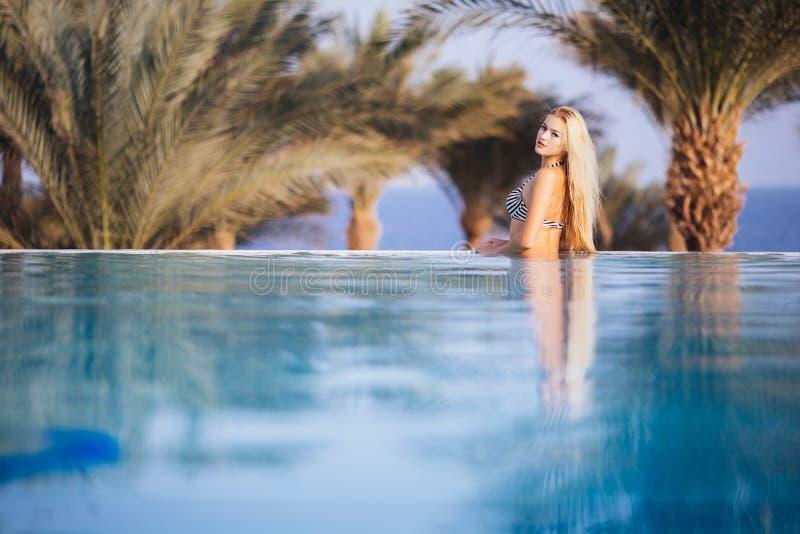 Centro turístico de lujo Mujer que se relaja en agua de la piscina del infinito Enjoying Summer Travel modelo femenino sano feliz fotos de archivo libres de regalías