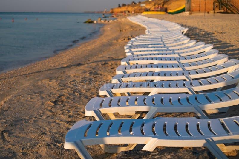 Centro turístico del mar con los ociosos blancos vacíos del sol Salida del sol en la playa fotografía de archivo libre de regalías