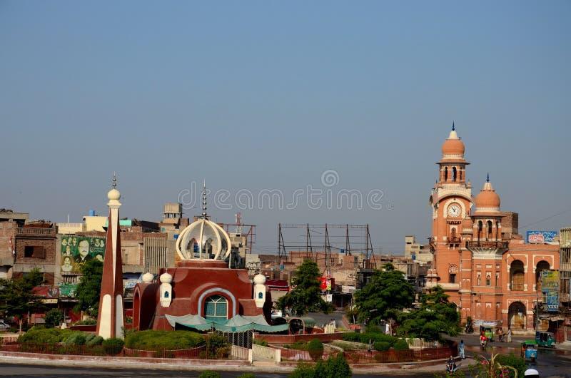 Centro urbano con la torre di orologio e moschea contemporanea alla rotonda Multan Pakistan fotografia stock