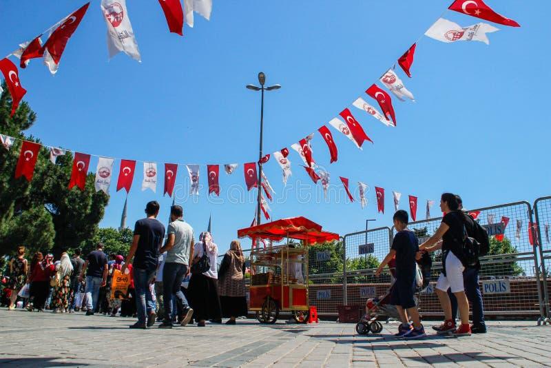 Centro urbano di Kadikoy con una folla della gente e delle bandiere turche che appendono sulle corde immagini stock libere da diritti