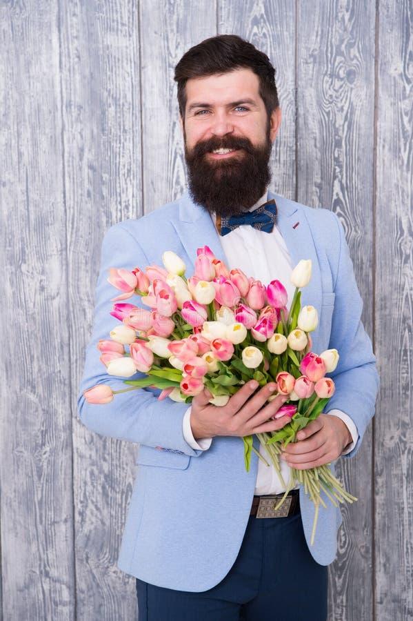 Centros de flores únicos Regalo de la primavera Inconformista barbudo del hombre con las flores Flor para el 8 de marzo Fecha del imagenes de archivo