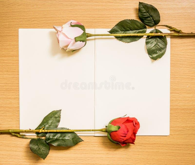 Centros de flores de Rose en la página blanca del libro imagen de archivo