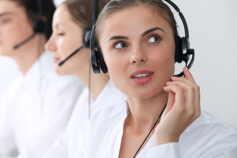 Centrum telefoniczne operatorzy przy pracą Ostrość przy piękną biznesową kobietą w słuchawki fotografia stock