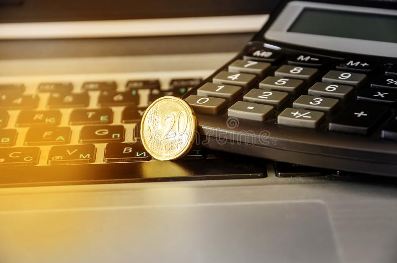 20 cents on a laptop keyboard. Coin and calculator on the keyboard, close-up. 20 cents on a laptop keyboard. Coin and calculator on the keyboard stock photos