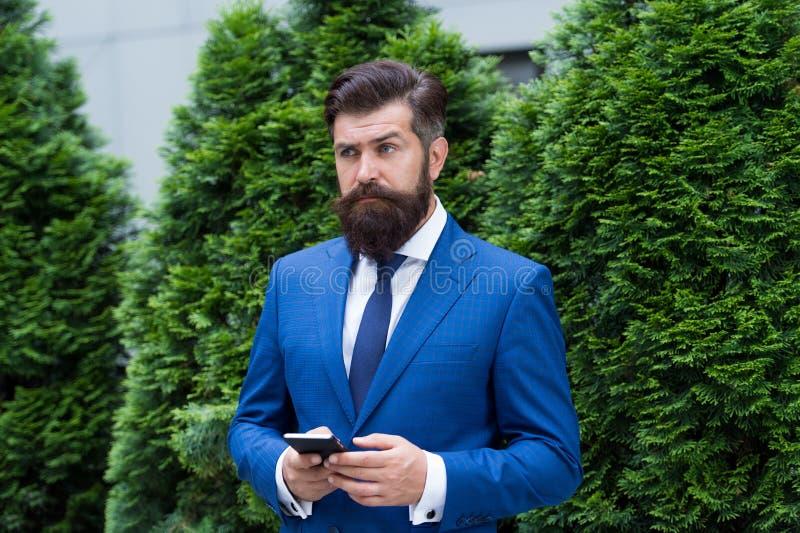 ceo现代神色  反应的电子邮件 r 有有些问题 与智能手机的严肃的商人 aglaia 图库摄影
