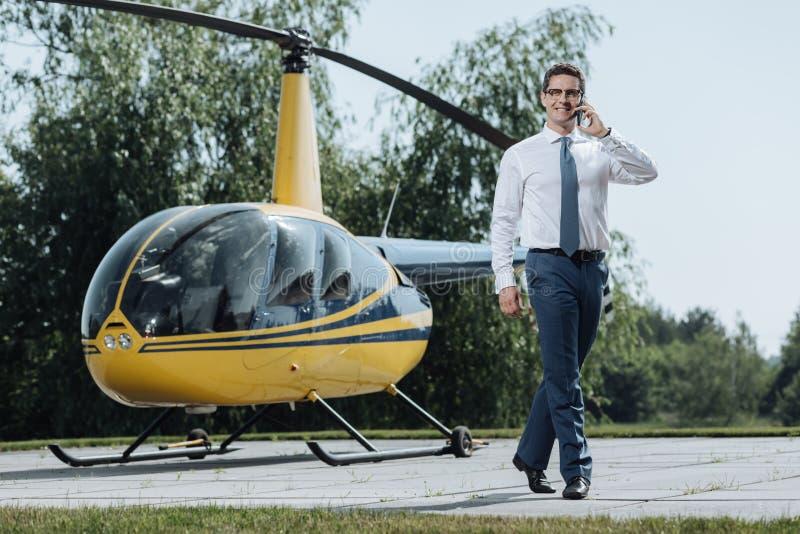 CEO alegre dos jovens que chama o táxi do heliporto fotografia de stock