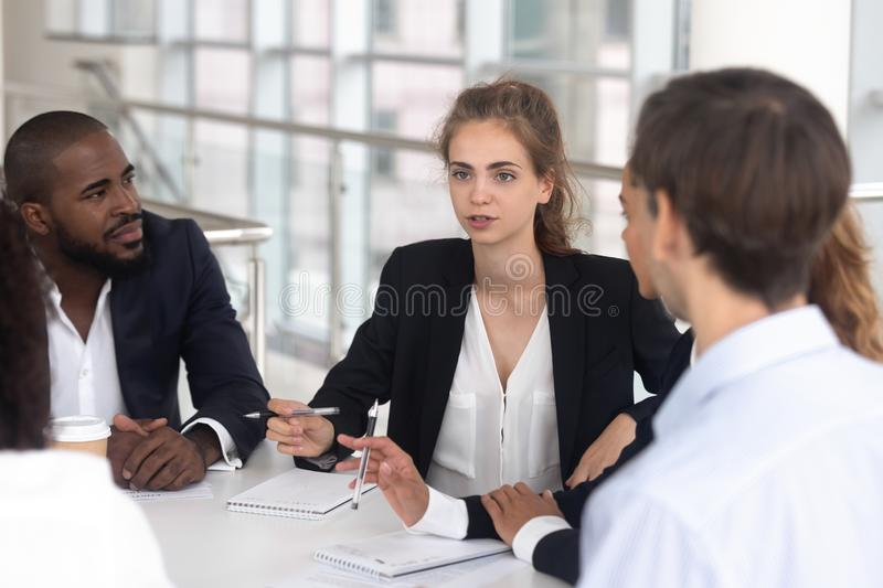 Female team leader discussing project plan at group multiracial briefing royalty free stock photography