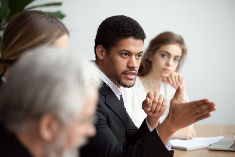 CEO do afro-americano que fala dando instruções na equipe diversa imagens de stock