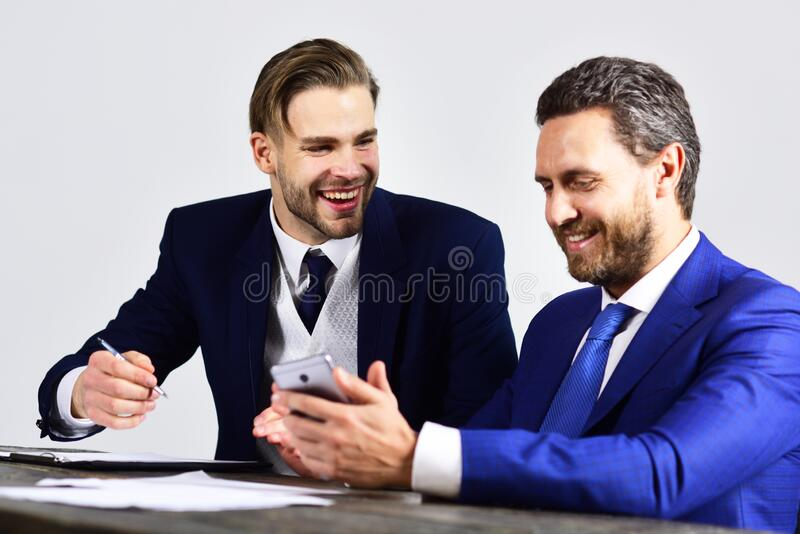 CEO and financial director discuss business solutions. Colleagues with cheerful faces surf internet. Director and businessman planning company strategy stock photography