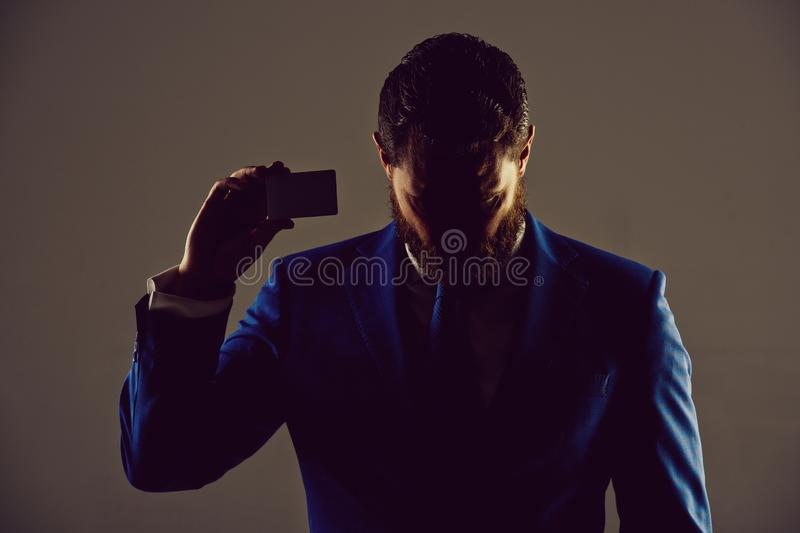 Ceo or man with business or credit card, business ethics. Shady business. ceo or man with business or credit card in blue formal outfit in shadow on grey stock photos